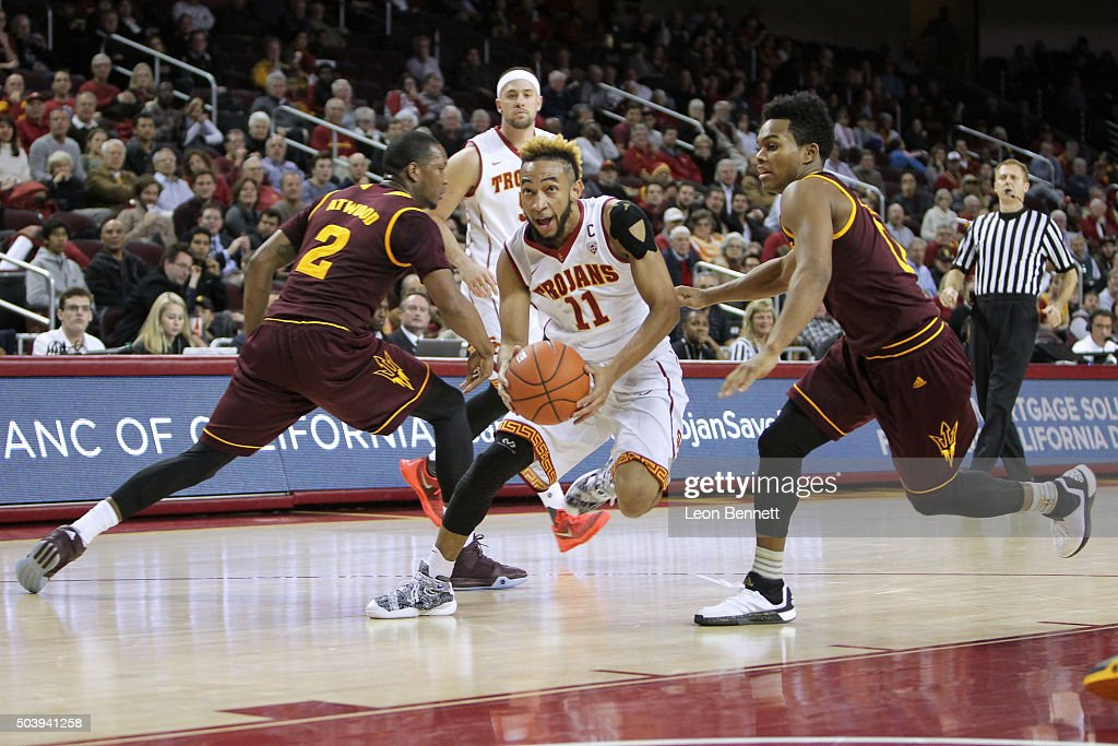Jordan McLaughlin #11 of the USC Trojans splits the defense of Willie Atwood #2 and Tra Holder #0 of the Arizona State Sundevils during a NCAA Pac12 college basketball game at Galen Center on January 7, 2016 in Los Angeles, California.
