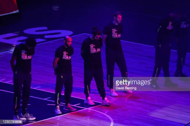 Jordan McLaughlin, Ricky Rubio, and Jake Layman of the Minnesota Timberwolves wear shirts supporting social justice during the national anthem before...
