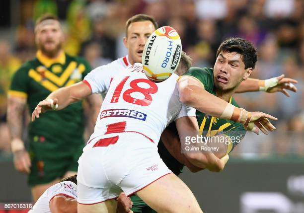 Jordan McLean of Australia passes the ball whilst being tackled during the 2017 Rugby League World Cup match between the Australian Kangaroos and...
