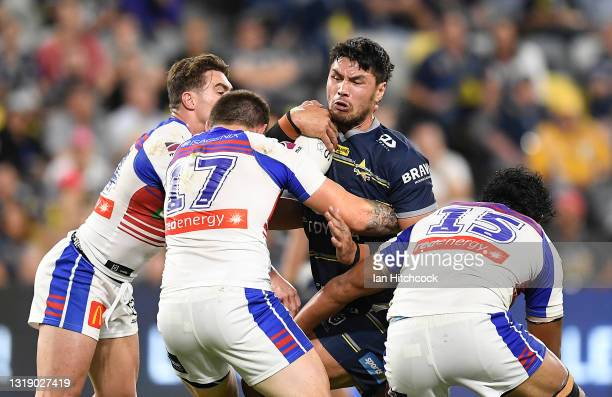 Jordan McLean of the Cowboys is tackled by Brodie Jones and Jacob Saifiti of the Knights during the round 11 NRL match between the North Queensland...