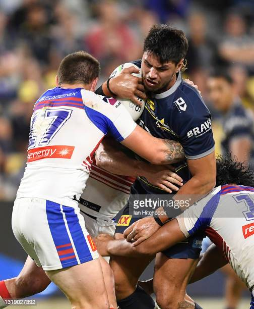 Jordan McLean of the Cowboys is tackled by Brodie Jones of the Knights during the round 11 NRL match between the North Queensland Cowboys and the...
