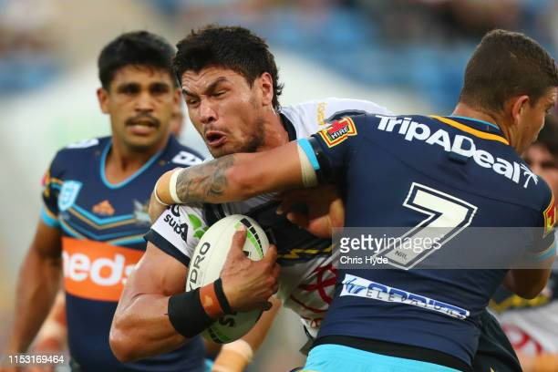Jordan McLean of the Cowboys is tackled by Jarrod Wallace of the Titans during the round 12 NRL match between the Gold Coast Titans and the North...