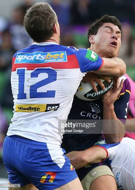 Jordan Mclean of the Storm gets tackled by Chris Houston of the Knights during the round 14 NRL match between the Melbourne Storm and the Newcastle...