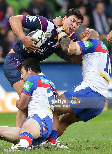 Jordan Mclean of the Storm gets tackled by Graig Gower and Jeremy Smith of the Knights during the round 14 NRL match between the Melbourne Storm and...