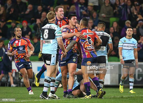 Jordan McLean of the Storm is congratulated by Tim Glasby and his teammates after scoring a try during the round 23 NRL match between the Melbourne...