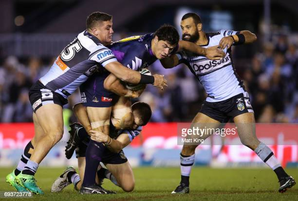 Jordan McLean of the Storm is tackled during the round 14 NRL match between the Cronulla Sharks and the Melbourne Storm at Southern Cross Group...