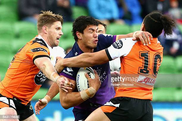 Jordan McLean of the Storm is tackled during the round 16 NRL match between the Melbourne Storm and Wests Tigers at AAMI Park on June 26 2016 in...