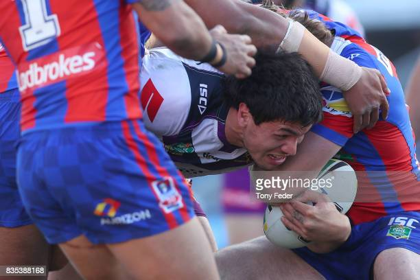 Jordan McLean of the Storm is tackled during the round 24 NRL match between the Newcastle Knights and the Melbourne Storm at McDonald Jones Stadium...