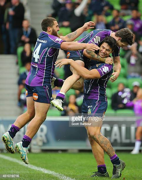 Jordan McLean of the Strom is congratulated by his teammates after scoring a try during the round 15 NRL match between the Melbourne Storm and the...