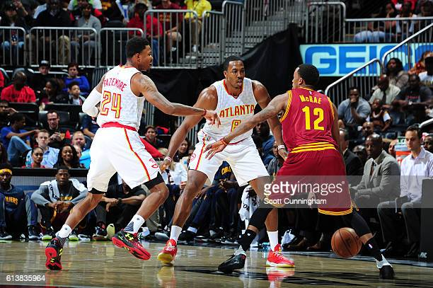 Jordan McRae of the Cleveland Cavaliers handles the ball against Dwight Howard and Kent Bazemore of the Atlanta Hawks during a preseason game on...