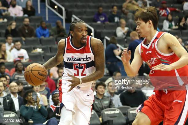 Jordan McRae of the Washington Wizards dribbles past Yue Wang of the Guangzhou LongLions during the second half at Capital One Arena on October 12...