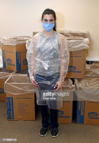 Jordan Mevius displays a disposable protective gown and surgical mask made at Polar Shades Sun Control as the company makes personal protective...