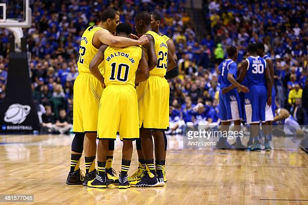 Jordan Morgan Derrick Walton Jr #10 and Caris LeVert of the Michigan Wolverines huddle with their team before their midwest regional final against...