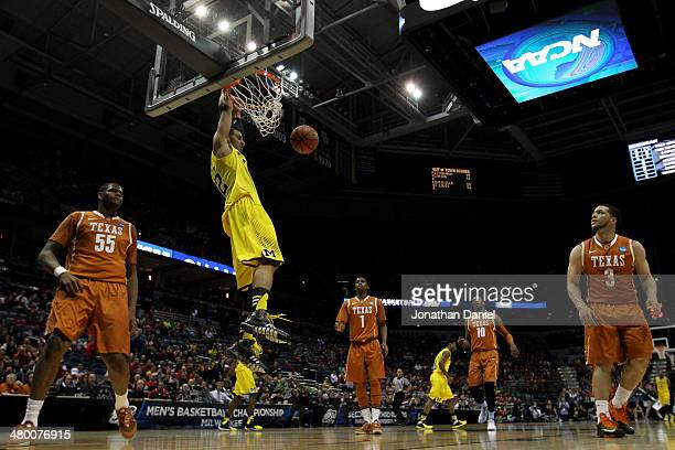 Jordan Morgan of the Michigan Wolverines dunks the ball against the Texas Longhorns during the third round of the 2014 NCAA Men's Basketball...