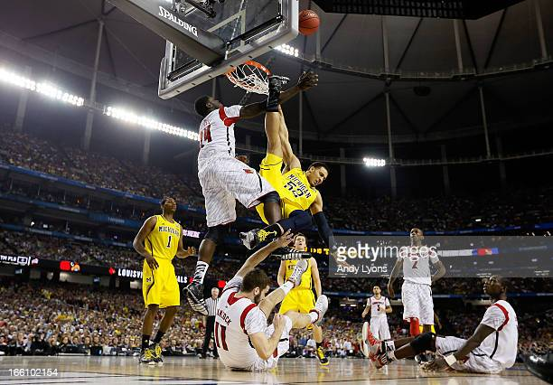 Jordan Morgan of the Michigan Wolverines falls to the court after he attempted a shot against Montrezl Harrell and Luke Hancock of the Louisville...