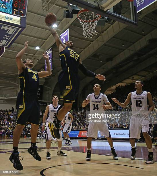 Jordan Morgan of the Michigan Wolverines goes up for a dunk over teammate Mitch McGary and Tre Demps and Jared Swopshire of the Northwestern Wildcats...