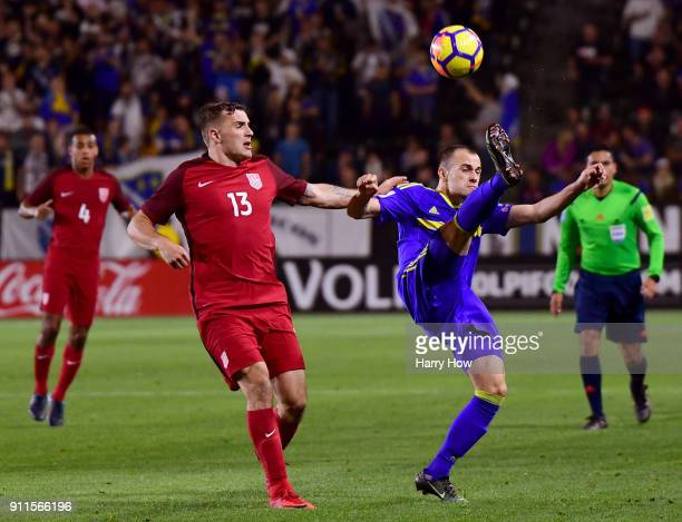 Jordan Morris of The United States chases Darko Todorovic of Bosnia Herzegovina as he clears during a 00 draw at StubHub Center on January 28 2018 in...