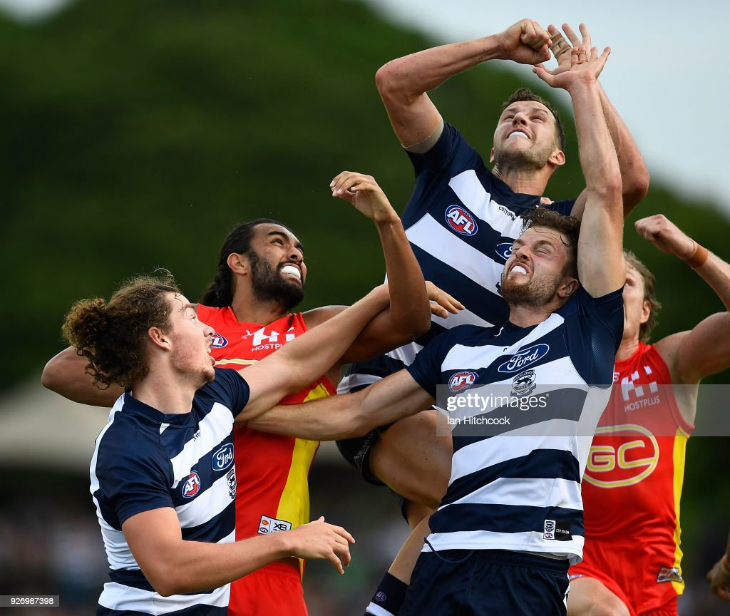 Jordan Murdoch and Wylie Buzza of the Cats contest the ball with Tom Nicholls of the Suns during the AFL JLT Community Series match between the Geelong Cats and the Gold Coast Suns at Riverway Stadium on March 4, 2018 in Townsville, Australia.