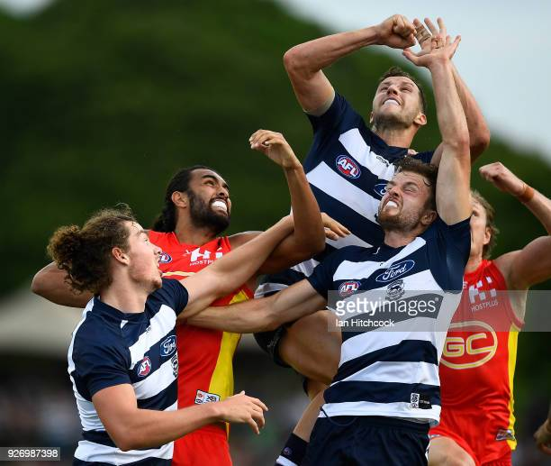 Jordan Murdoch and Wylie Buzza of the Cats contest the ball with Tom Nicholls of the Suns during the AFL JLT Community Series match between the...