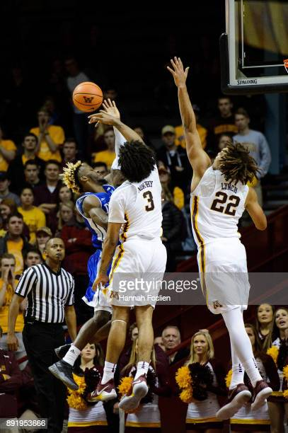 Jordan Murphy and Reggie Lynch of the Minnesota Golden Gophers blocks a shot by Ore Arogundade of the Drake Bulldogs during the game on December 11...