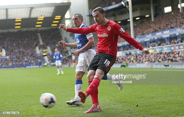 Jordan Mutch of Cardiff City shoots away from Leon Osman of Everton during the Barclays Premier League match between Everton and Cardiff City at...
