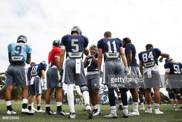 Jordan Myers tralks to team mates eduring a Rice University College Football training session at David Phillips Sports Complex on August 24, 2017 in...