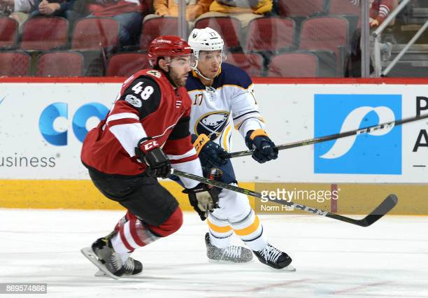 Jordan Nolan of the Buffalo Sabres and Jordan Martinook of the Arizona Coyotes skate for the puck during the first period at Gila River Arena on...