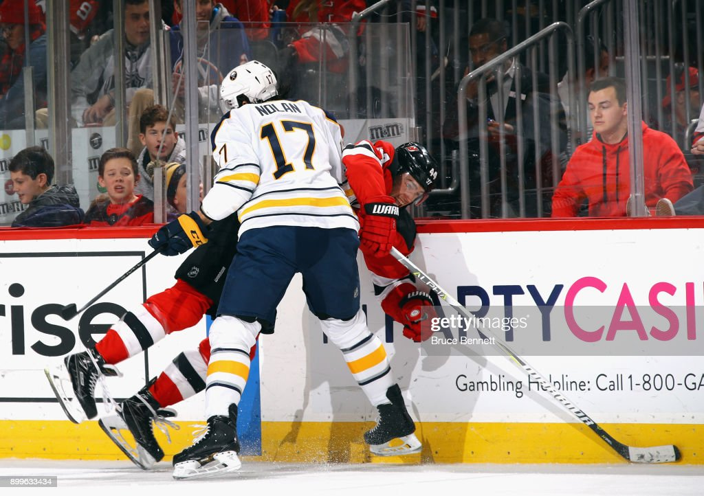 Jordan Nolan #17 of the Buffalo Sabres checks Miles Wood #44 of the New Jersey Devils during the second period at the Prudential Center on December 29, 2017 in Newark, New Jersey.