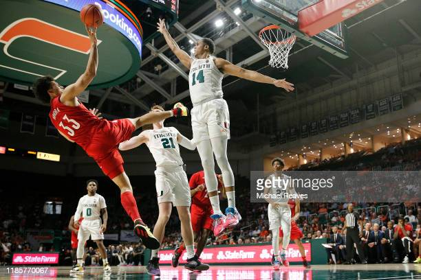 Jordan Nwora of the Louisville Cardinals attempts a shot against the Miami Hurricanes during the second half at Watsco Center on November 05, 2019 in...