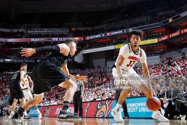 Jordan Nwora of the Louisville Cardinals handles the ball against Ernie Duncan of the Vermont Catamounts in the second half of the game at KFC YUM...