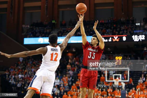 Jordan Nwora of the Louisville Cardinals shoots over De'Andre Hunter of the Virginia Cavaliers in the first half during a game at John Paul Jones...
