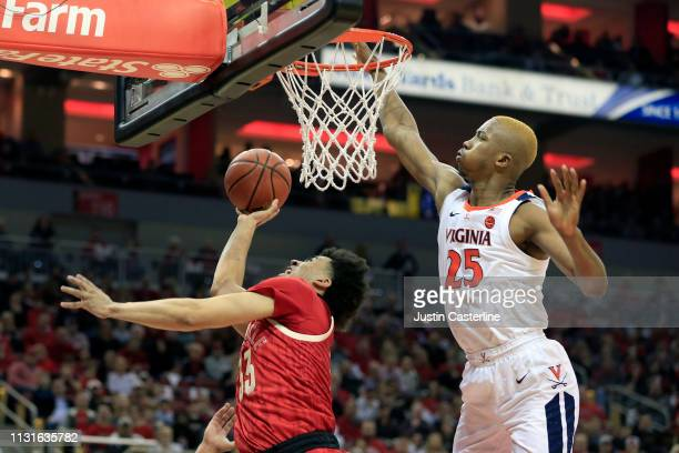 Jordan Nwora of the Louisville Cardinals shoots the ball while being guarded by Mamadi Diakite of the Virginia Cavaliers during the first half at KFC...