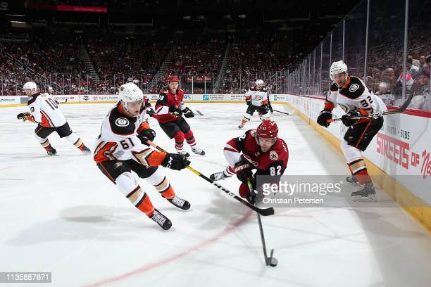 Jordan Oesterle of the Arizona Coyotes attempts to play the puck pressured by Troy Terry of the Anaheim Ducks during the third period of the NHL game...