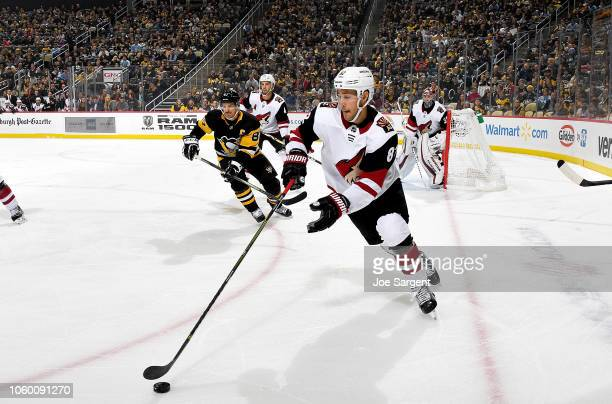 Jordan Oesterle of the Arizona Coyotes handles the puck against Sidney Crosby of the Pittsburgh Penguins at PPG Paints Arena on November 10 2018 in...