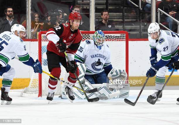 Jordan Oesterle of the Arizona Coyotes looks to play the puck in front of goalie Thatcher Demko of the Vancouver Canucksas as Alex Biega and Ben...