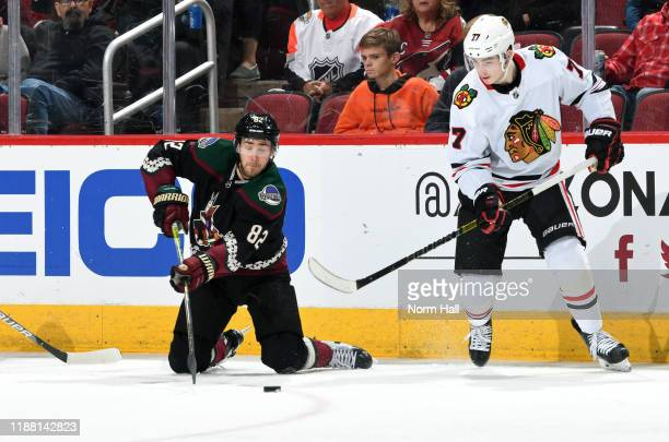 Jordan Oesterle of the Arizona Coyotes plays the puck from his knees in front of Kirby Dach of the Chicago Blackhawks during the second period of the...