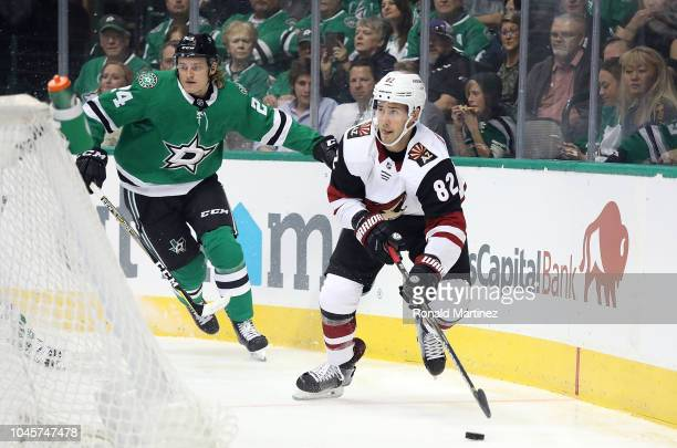 Jordan Oesterle of the Arizona Coyotes skates the puck against Roope Hintz of the Dallas Stars in the first period at American Airlines Center on...