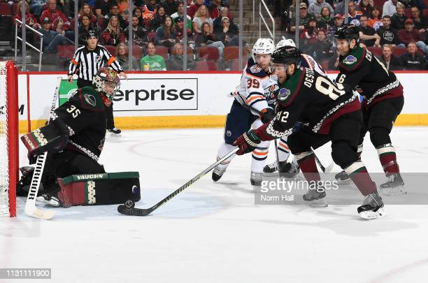 Jordan Oesterle of the Arizona Coyotes tries to clear the puck away from goalie Darcy Kuemper of the Coyotes as Alex Chiasson of the Edmonton Oilers...