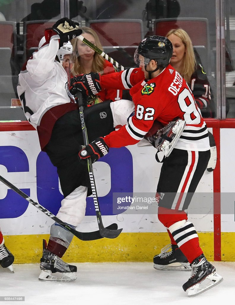 Jordan Oesterle #82 of the Chicago Blackhawks hits Alexander Kerfoot #13 of the Colorado Avalanche at the United Center on March 20, 2018 in Chicago, Illinois. The Avalanche defeated the Blackhawks 5-1.