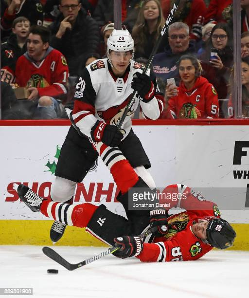 Jordan Oesterle of the Chicago Blackhawks hits the ice after being tripped by Dylan Strome of the Arizona Coyotes at the United Center on December 10...