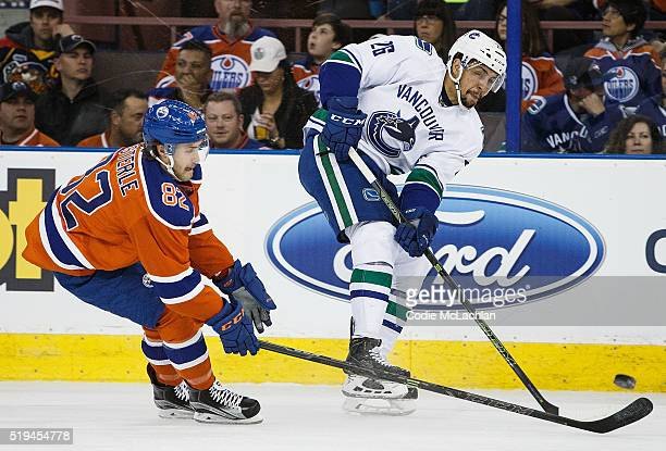 Jordan Oesterle of the Edmonton Oilers defends against Emerson Etem of the Vancouver Canucks on April 6 2016 at Rexall Place in Edmonton Alberta...