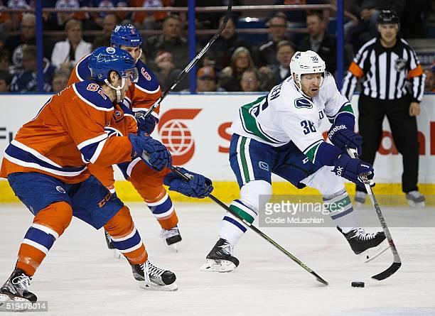 Jordan Oesterle of the Edmonton Oilers defends against Jannik Hansen of the Vancouver Canucks on April 6 2016 at Rexall Place in Edmonton Alberta...