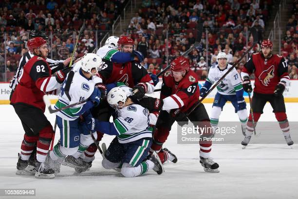 Jordan Oesterle Oliver EkmanLarsson and Lawson Crouse of the Arizona Coyotes are invoved in a scrum with Jake Virtanen and Antoine Roussel of the...