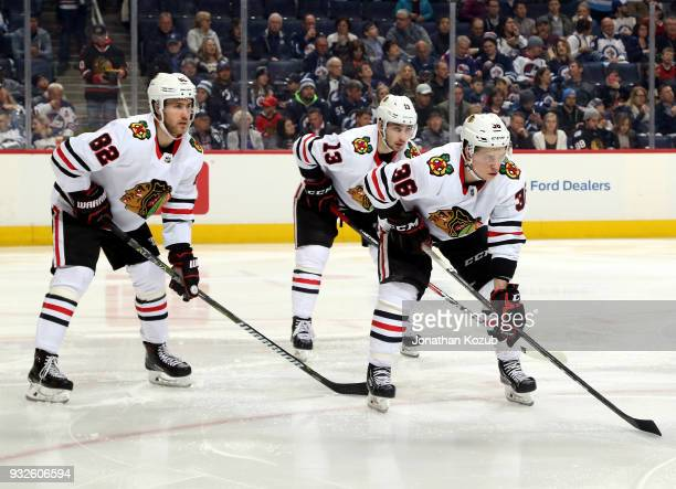 Jordan Oesterle Tomas Jurco and Matthew Highmore of the Chicago Blackhawks get set for a second period faceoff against the Winnipeg Jets at the Bell...