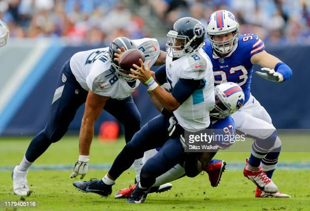 Jordan Phillips of the Buffalo Bills tackles Marcus Mariota of the Tennessee Titans while he looks to pass during the first quarter at Nissan Stadium...