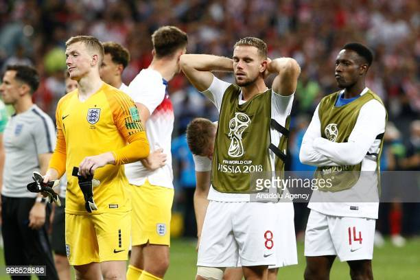 Jordan Pickford and Jordan Henderson and Danny Welbeck of England react after the 2018 FIFA World Cup Russia Semi Final match between England and...