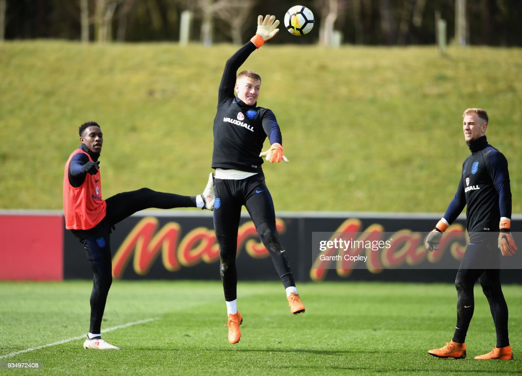 Jordan Pickford clears the ball as Joe Hart and Danny Welbeck watch on during an England training session at St Georges Park on March 20, 2018 in Burton-upon-Trent, England.