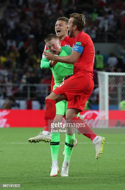 Jordan Pickford of England is mobbed by Harry Kane and Kieran Trippier in celebration after England win the penalty shootout following the 2018 FIFA...