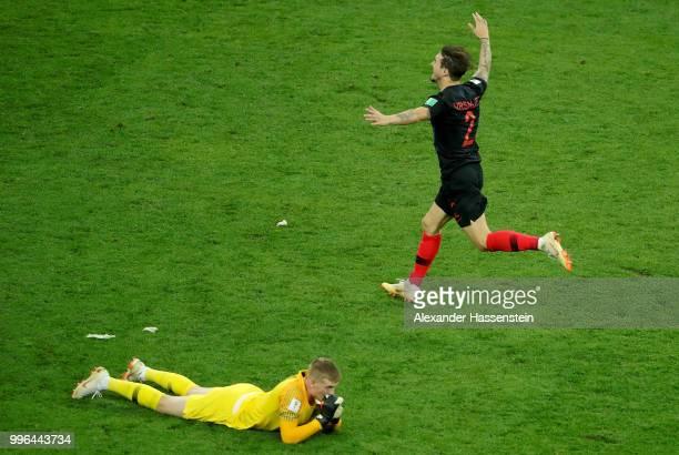 Jordan Pickford of England lies on the floor dejected as Sime Vrsaljko of Croatia celebrates winning the 2018 FIFA World Cup Russia Semi Final match...