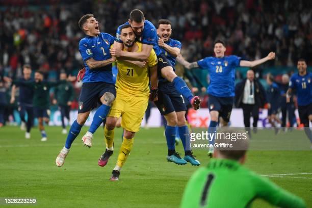 Jordan Pickford of England looks on dejected as Giovanni Di Lorenzo, Gianluigi Donnarumma, Andrea Belotti, and Alessandro Florenzi of Italy celebrate...